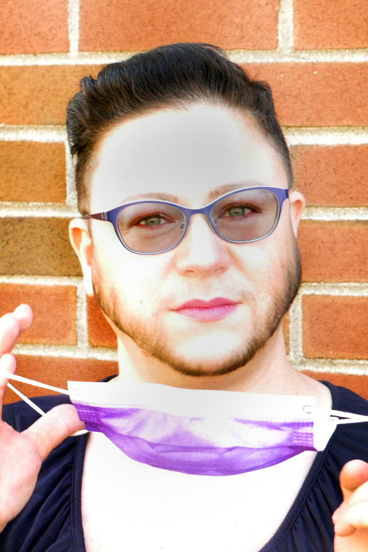 Headshot of Faye with glasses, a beard, & lipstick, with a purple mask in their hands, in front of a brick background